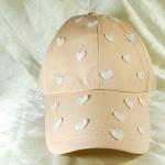 หมวกแก๊ป Cap สีครีม แต่งหัวใจสีขาวเหลือบเงิน เต็มหน้าหมวก